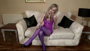 Tanned blonde chick in stockings, Capri is playing with a huge purple sex toy, on the sofa